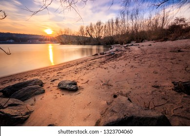 winter landscape. colorful sunset over the river rhine. with sandy bay and in a long exposure. soft water