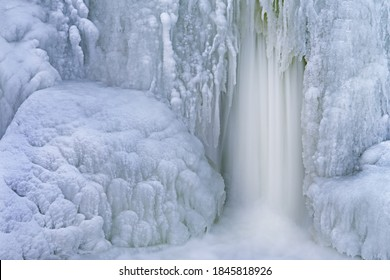 Winter landscape of the Comstock Creek cascade framed by ice and captured with motion blur, Michigan, USA