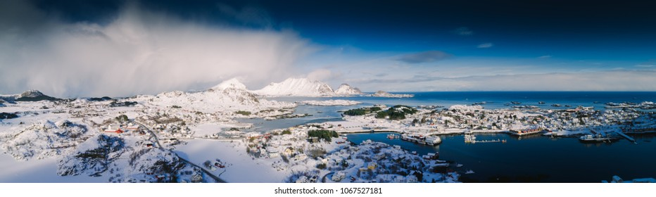 Winter landscape with deep blue sky and contrasty white clouds panorama of small fishing village