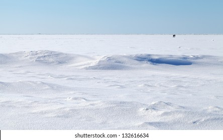 Winter landscape. Deep blue sky and snow on frozen Baltic Sea with people walking on ice