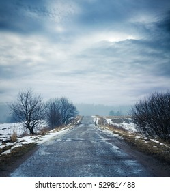 Winter Landscape. Dirty Road, Fog and Moody Sky. HDR Styled Dramatic Clouds. Toned Photo with Copy Space.