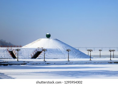Winter landscape of the Dnipro city Waterfront with vintage lanterns.  The Dnieper River and the pyramid are covered with snow and ice. Dnepropetrovsk, Ukraine.