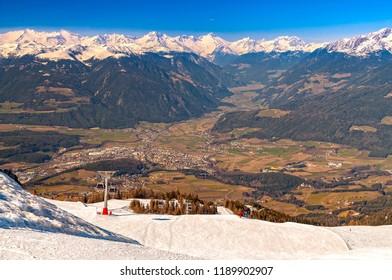 Winter landscape in Dolomites at Plan de Corones / Kronplatz ski resort, Italy with Brunico/Bruneck town in background