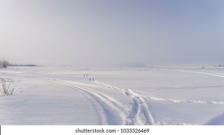 Winter landscape. Field under the snow. above the trees the fog. Winter road. Morning