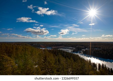 Winter landscape from Finland. The picture is taken high. The sun is bright and the sky is blue.