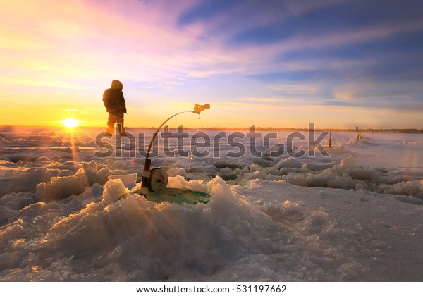 winter landscape fishermen on the ice of the river at sunset
