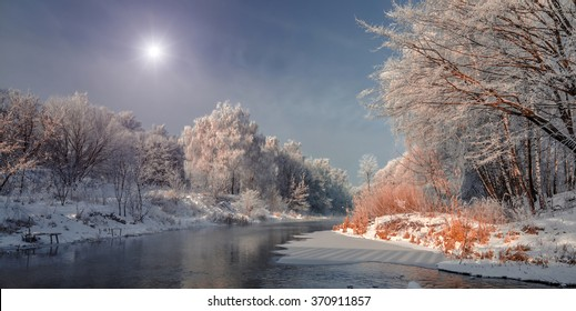 winter landscape. Frosty, misty morning on the small river. frost covered tree in the warm glow of sunrise on the beach. The beauty of the world.  Europe. Ukraine  frozen lake and trees in snow