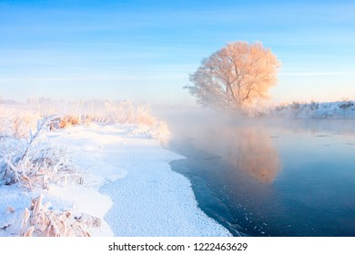 Winter landscape in frosty morning. Tree covered with hoarfrost on blue sky background illuminated by rising winter sun. Snowy riversides with ice. Beautiful christmas day. Natural winter background.