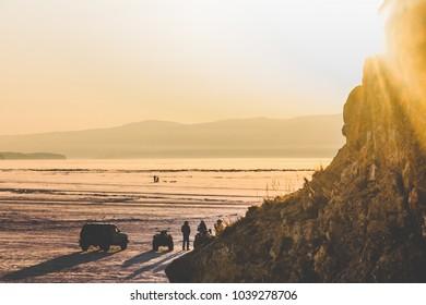 Winter landscape, frozen Lake Baikal, Irkutsk, Siberia, Russia. Snowy. Beautiful wallpaper with nature scene: golden sunset, sun shining out of the rock, people standing nearby a car, shadows.