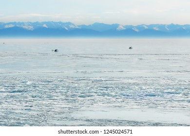 winter landscape with frozen lake and blue mountain range in the distance; two hovercrafts in the middle of ice field