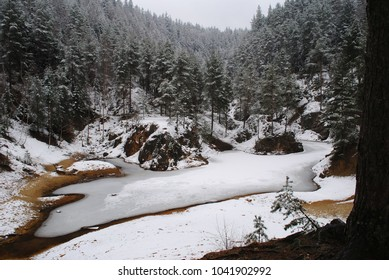 Winter landscape of frozen lake. Ice on pond located in between mountains with snowy peaks. Many trees, mostly coniferous. Cold season recreation view. Visible brown shore of water natural formation.