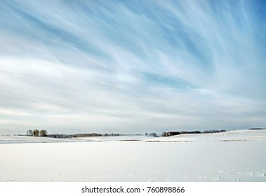 Winter landscape with frozen pond between snowy fields