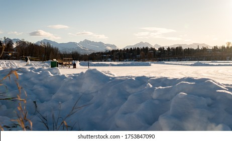 Winter landscape of frozen Westchester Lagoon and the mountains of Chugach Park in the back. Taken from Margaret Eagan Sullivan Playground. Near downtown Anchorage, Alaska. Covered with snow. Sunrise.