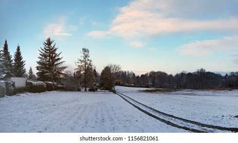 Winter landscape in Germany, Dresden. Snow field with long direct road goes into the distance, forest trees and countryside houses on the right and left sides, blue cold sky with clouds
