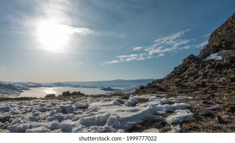Winter landscape. A granite rock devoid of vegetation. Snow on the ground. Sun and clouds in the blue sky. In the distance, a frozen lake surrounded by mountains. Reflections on an icy surface. Baikal