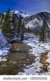 Winter landscape of high mountain peaks and alpine forest covered with freshly fallen snow with river running up the valley