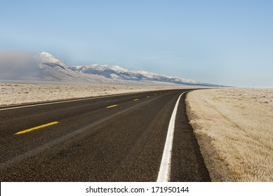 A winter landscape of a highway running through the Lemhi Valley along the Lemhi Mountain Range in Central Idaho.