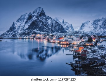 Winter landscape with houses in village, city illumination, snowy mountains, sea, blue cloudy sky reflected in water at dusk. Beautiful Reine at night, Lofoten islands, Norway. Norwegian rorbuer