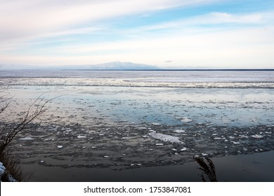 Winter landscape of ice floes floating on Knik Arm from Point Woronzof Park while following Tony Knowles Coastal Trail in Anchorage, Alaska. Taken in winter. Climate change; ice melting.