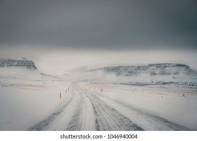 Winter landscape of Iceland's road during snowstorm with the snow-capped mountain as a background and frozen road as a foreground.