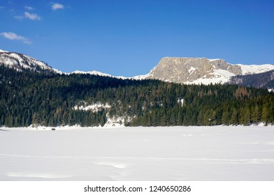Winter landscape with a lake covered in tall powder snow and mountain peaks in the background. Black Lake (Crno jezero) in Zabljak, Montenegro.