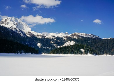 Winter landscape with a lake covered in untouched powder snow and tall mountain peaks in the background. Bobotov Kuk peak as seen from Black Lake (Crno jezero) in Zabljak, Montenegro.
