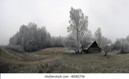 Winter landscape with a lonely small house and the trees covered by hoarfrost.