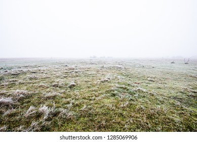 Winter landscape. Misty morning field, frost and snow on the grass. Latvia