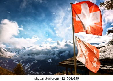 Winter landscape with mountain peaks and Swiss flag. Nature background