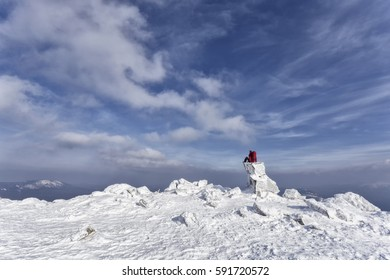 Winter landscape in the mountains. Clouds in the sky, sunny day. Lots of snow, frost, cold, space. Ural Mountains, Russia. Girl woman sitting on a stone and looks at mountains
