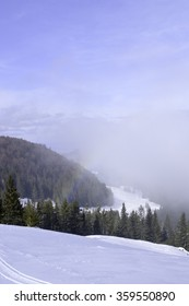 Winter landscape in the mountains with snow covered forest and blue cloudy sky