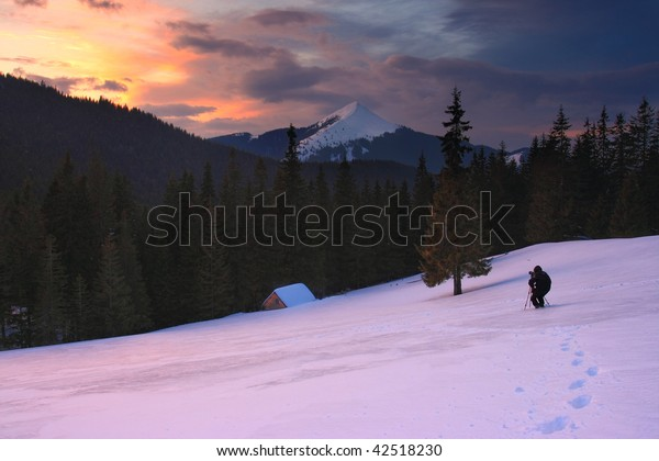 winter landscape with mountains under evening sky with clouds