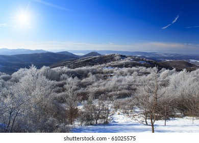 Winter landscape, mountens with frozen trees and blue sky in Hungary