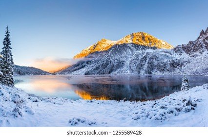Winter landscape. Winter natural background. Mountains with snow covered hills and sunny peaks by the lake. Tatras, Zakopane, Poland.