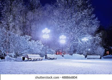 Winter landscape - night snowy park lit by street lanterns and benches covered with snow