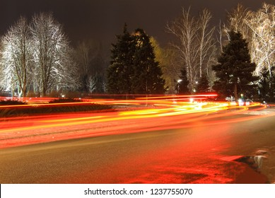 Winter landscape, night traffic with blurred car tracks against the background of a park in the  Dnipro city  in evening, Dnepropetrovsk, Ukraine
