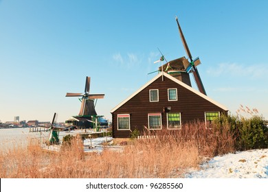 Winter landscape of old dutch village with windmills in snow on beautiful clear day. Blue sky.