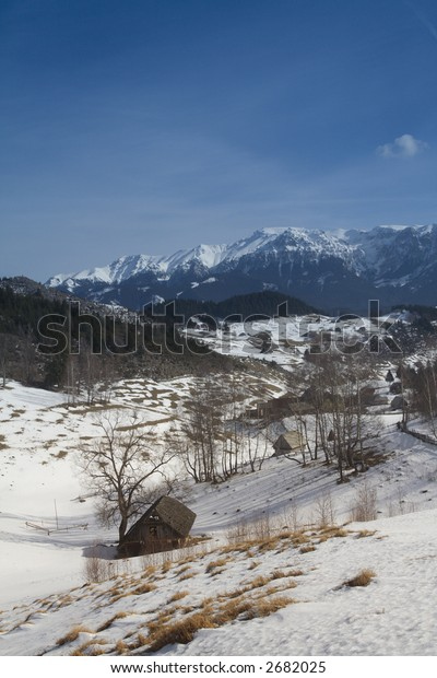 Winter landscape with old houses, blues sky and sunny day