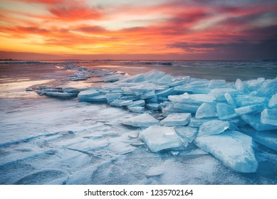 Winter landscape on seashore during sunset. Lofoten islands, Norway. Ice and sunset sky. Natural winter landscape