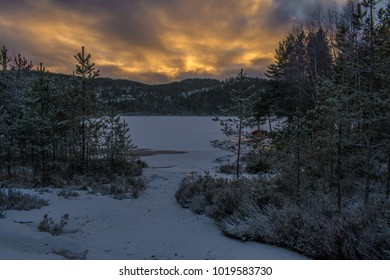 Winter landscape photo of Vigeland in Norway.  The water is frozen and the sun is rising behind the mountains and the fog slips away.
