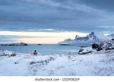 Winter landscape with photographer on the Lofoten islands, Norway, Europe