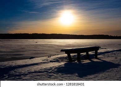 Winter landscape picture in Finland. Empty park bench in front. A frozen lake in the background.
