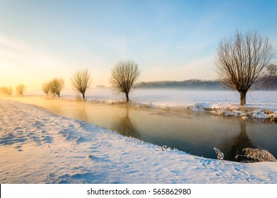 Winter landscape of a polder with a frozen stream in the Netherlands. It is early in the morning of a beautiful day, the sun is rising and some morning mist is still visible above the field.