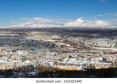 Winter landscape residential buildings of Petropavlovsk-Kamchatsky City, scenery volcanoes of Kamchatka Peninsula: Koryak Volcano, Avacha Volcano, Kozelsky Volcano on clear sunny day with blue sky.