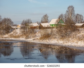 Winter landscape with the river in frosty day. Old wooden rural house situated on the bank of the river