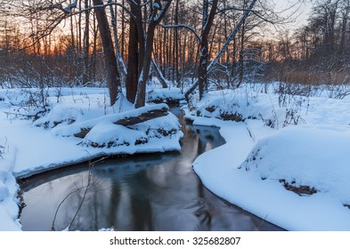 Winter landscape with a river in the woods in the evening at sunset