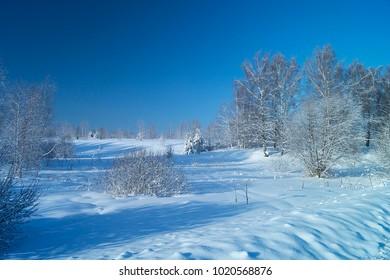 Winter landscape in rural terrain on background blue sky