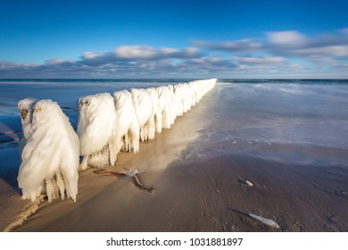 Winter landscape at the sea. Frozen wooden breakwaters line at Baltic Sea. Morning at Chalupy, Poland.