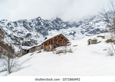 Winter landscape with ski huts. Winter holiday house. Aosta Valley Monterosa Gressoney. Cabin covered with snow. Mountain hut. winter season,Big mountain cabin. Alpine panorama with Walser huts