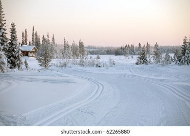 winter landscape with ski route and wooden house